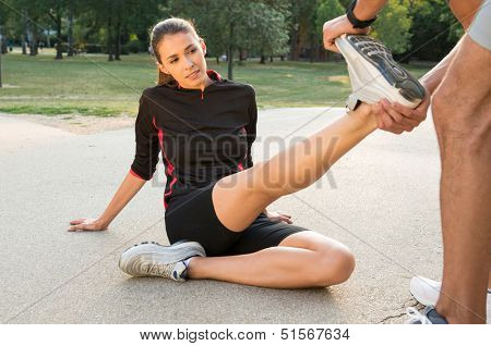 Male Fitness Instructor Straightening Woman's Leg