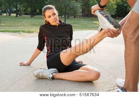 Male Fitness Instructor Straightening Woman's Leg