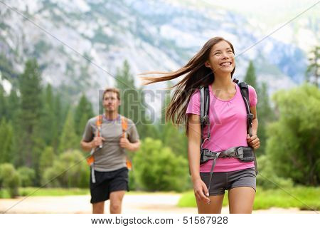 People hiking - happy hikers on hike trekking travel trek during summer vacations outdoors in beautiful forest mountain landscape in Yosemite national park, California, USA. Man and woman together.