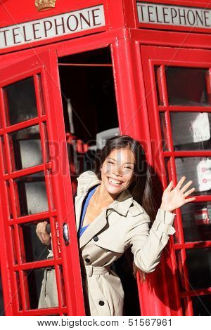 London red phone booth - woman waving happy peaking out excited looking at camera saying hello. Beautiful smiling young female in London, England, United Kingdom.