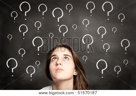 young girl looking chalkboard with interrogation symbols