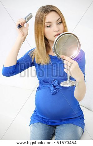 Beauty pregnant woman doing makeup on the white background.