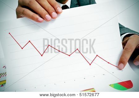 man wearing a suit sitting in a table showing a graph of economic losses
