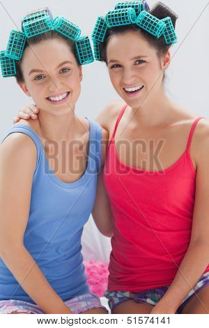 Girls in hair rollers sitting in bed and smiling at camera at sleepover