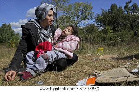 SOFIA, BULGARIA, 20 SEPTEMBER 2013 - Unknown Syrian mother, holding her sick child is sitting on the grass near a refugee camp in Sofia, Bulgaria.