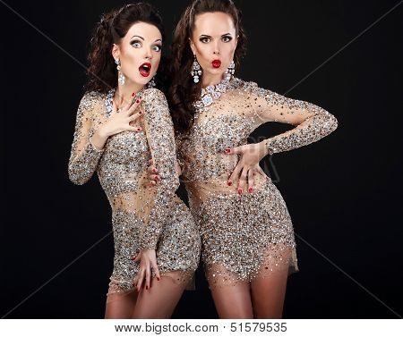 Soiree. Two Young Surprised Women Over Black