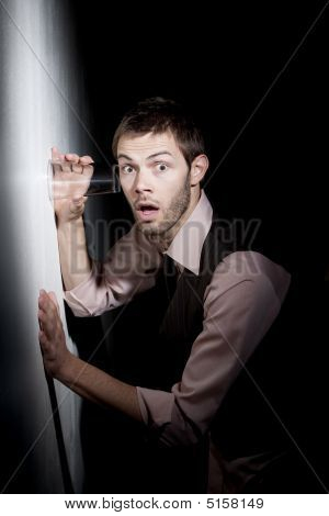 Handsome Young Man Using Glass To Eavesdrop