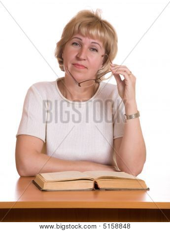 The Mature Woman With  Book Behind A Table