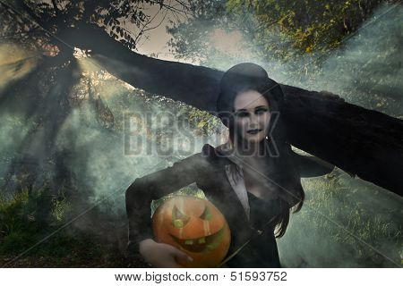 Halloween concept: sexy lady vampire with pumpkin in forest