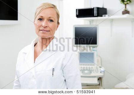 Portrait of mid adult female radiologist standing in examination room