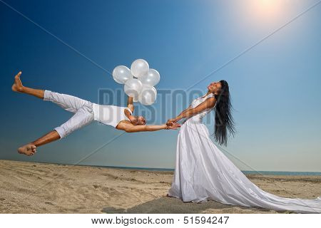 Happy groom flying to his sweetheart on the beach