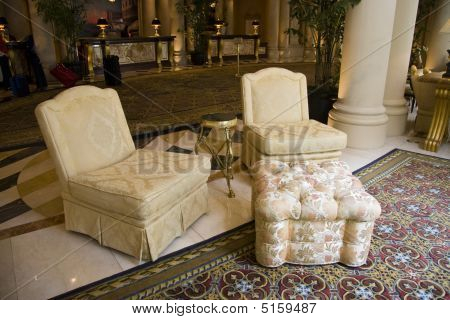Two Beige Armchairs And Pouffe