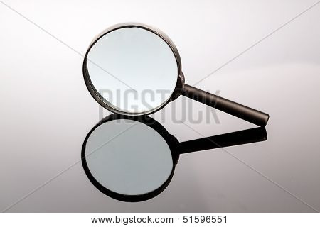 a magnifying glass lying on a gray background and reflected