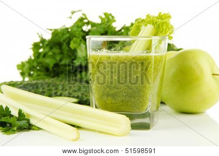 Glass of green vegetable juice and vegetables close up