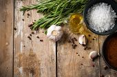 stock photo of ingredient  - Different spices rosemary allspice garlic oil and salt on a wooden board rustic kitchen background - JPG