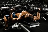 image of execution  - very powerful athletic guy executes  presses with dumbbells in gym - JPG