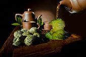 pic of loam  - horizontal photo of the clay teapot tea flow in cup on brown background tea ceremony - JPG