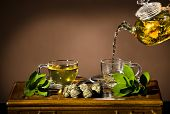 stock photo of infusion  - horizontal photo of the glass teapot flow green tea in cup on brown background tea ceremony - JPG