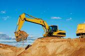 foto of dumper  - excavator machine loading dumper truck at sand quarry - JPG