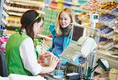 stock photo of cashiers  - Customer buying food at supermarket and making check out with cashdesk worker in store - JPG