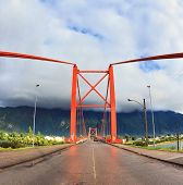 Patagonia, Chile. Red bridge over the fjord. A gorgeous summer day and a huge cloud. The picture was