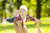 Cute little baby in the park with mother on the grass. Sweet baby and mom  outdoors. Smiling emotion
