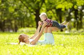 stock photo of mums  - Cute little baby in summer  park with mother  on the grass - JPG