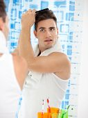 pic of frot  - young man to comb frot of mirror in bath room - JPG