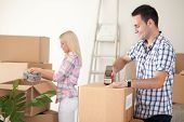 stock photo of independent woman  - young couple packing moving boxes - JPG