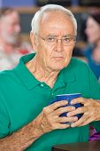 picture of sulky  - Sulky senior male holding coffee mug in cafe - JPG