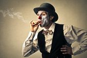 image of bowler  - funny clown with bowler hat smokes a cigar - JPG