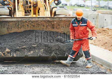 builders workers at asphalting paver machine during Road street repairing works