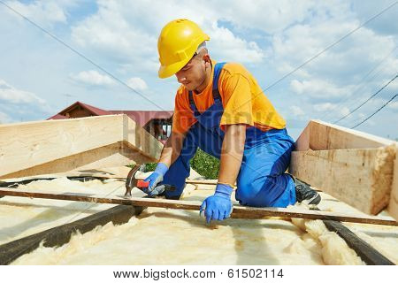 construction roofer carpenter worker hammering wood board with hammer and nail on roof installation work