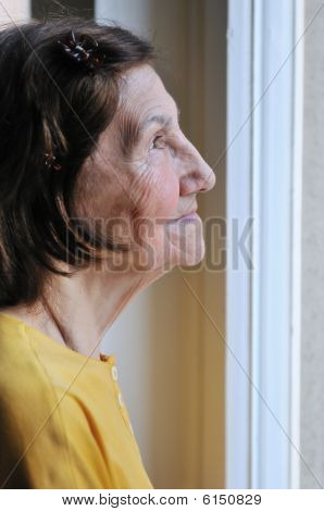 Solitude - Senior Woman Looking Through Window
