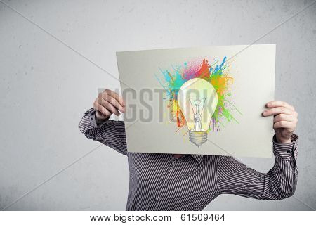 Businessman holding a cardboard with coloured paint splashes and lightbulb in front of his head