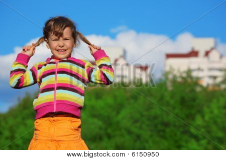 little girl holding plaits in front of trees and buildings