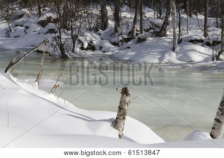 Frozen river in the winter forest. One of the tributaries of Lake Baikal