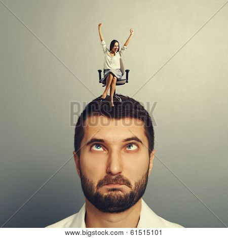 happy woman sitting on the stressed man over grey background