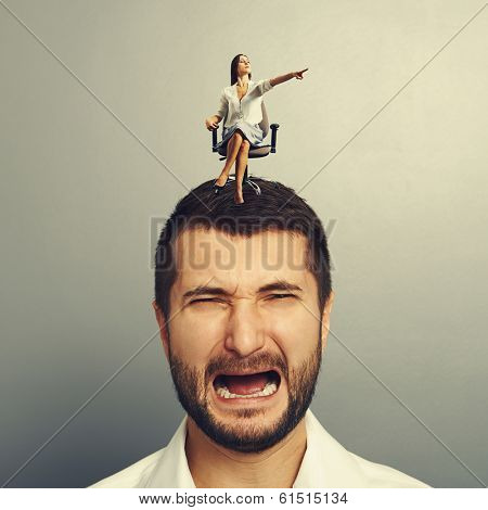 small serious woman sitting on the discontented man and pointing at something over dark background