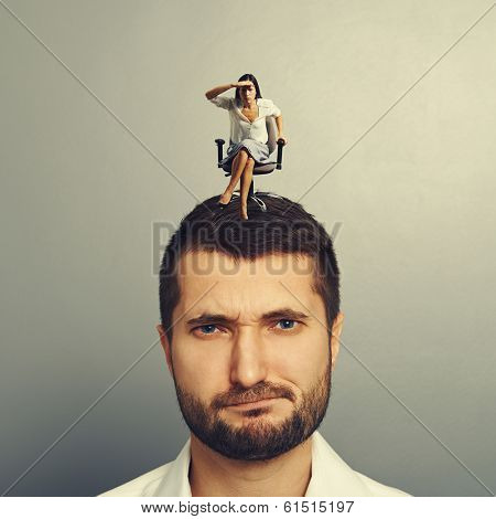 concentrated woman siting on the dissatisfied man and looking into the distance