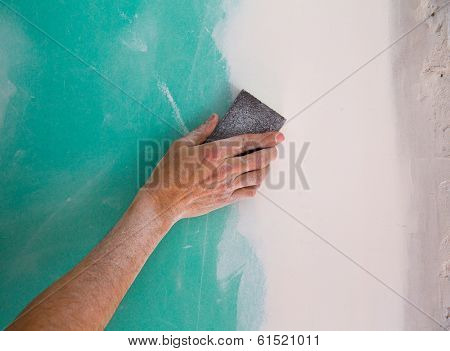 plastering man hand sanding the plaste in drywall seam plasterboard