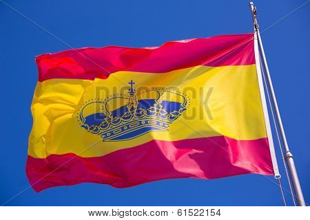 Spain red and yellow flaw waving on wind under blue sky