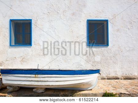 Mediterranean boat and whitewashed wall in white and blue at Balearic Islands