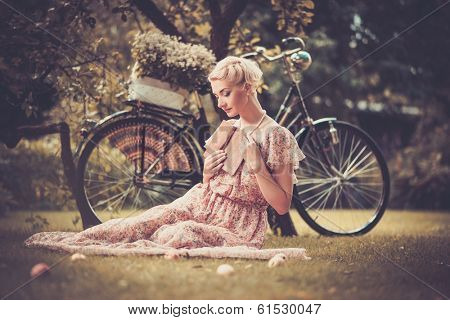 Dreaming blond retro woman with a book in summer dress sitting on a meadow