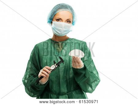 Plastic surgeon woman with silicon breast implants and calliper