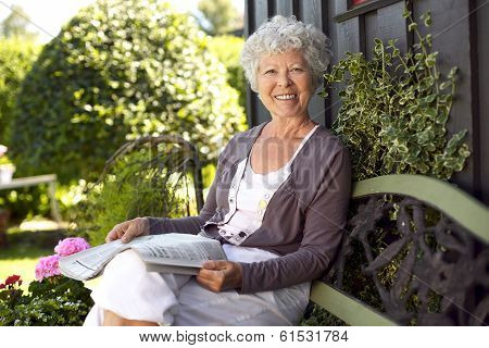 Happy Senior Woman Reading Newspaper In Her Backyard
