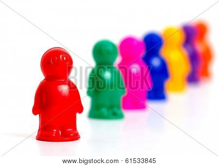 Colorful toy people standing in a queue