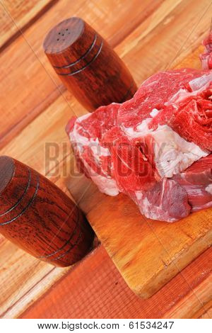 fresh raw uncooked beef fillet mignon entrecote on board prepared for cooking on wood table wtih cutlery and castors