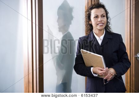 Confident Hispanic businesswoman in boardroom, colleague outside