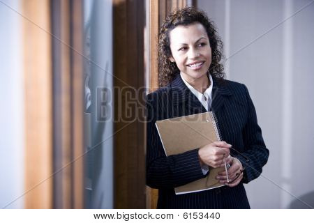 Confident Hispanic businesswoman standing in boardroom